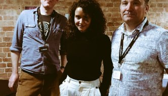 emma grazette is stood between two men after winning a documentary pitch during Two Short Nights in Exeter