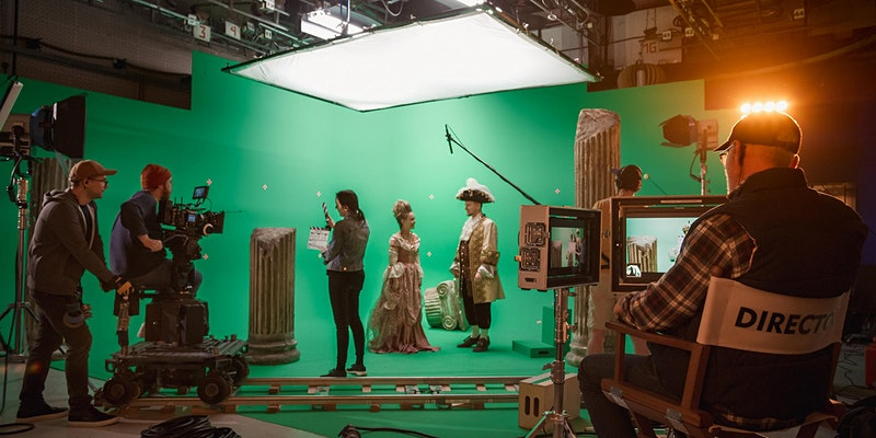 a director working with actors on a green stage
