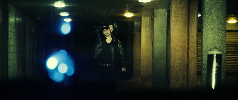 a man is in an underpass at night, holding his hand up against the glare of car headlights