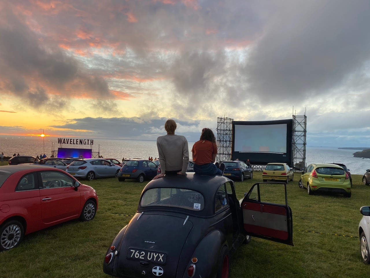people sitting on their cars looking at a clifftop drive in