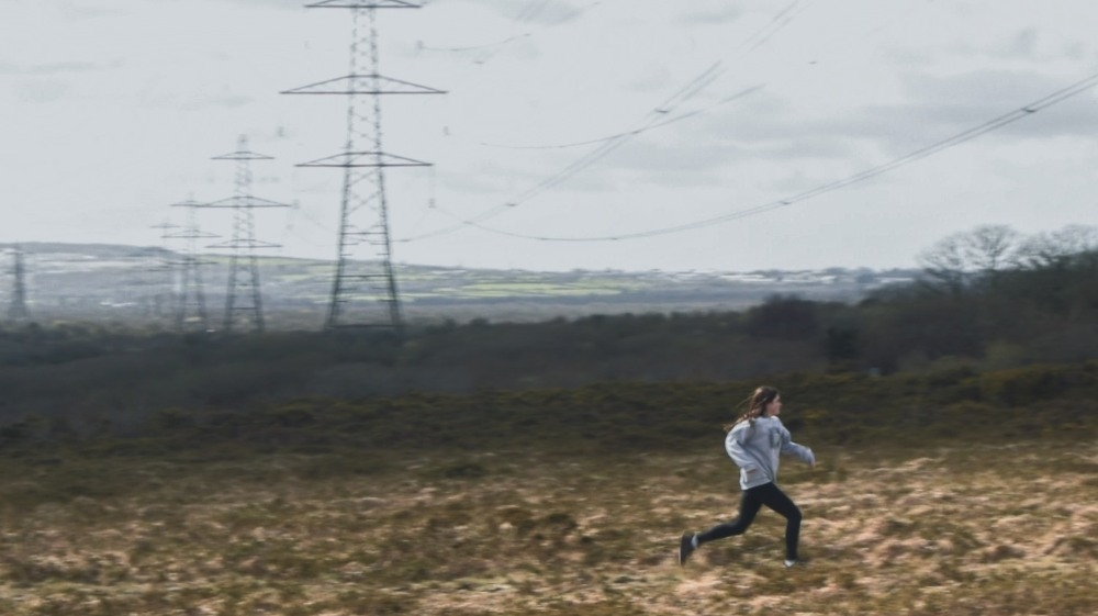a picture of a young girl running in a field there are electricity pylons behind her