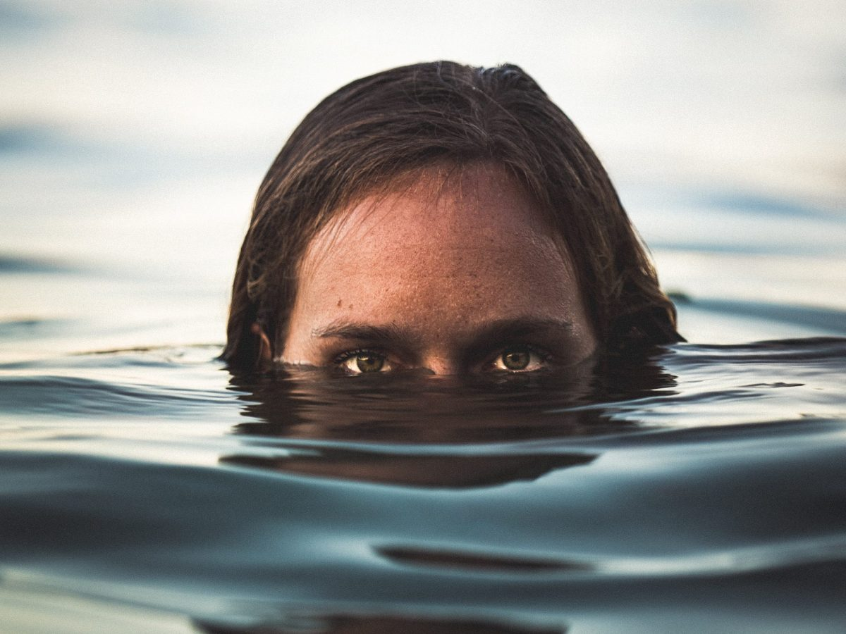 Intense woman's eyes appearing from water