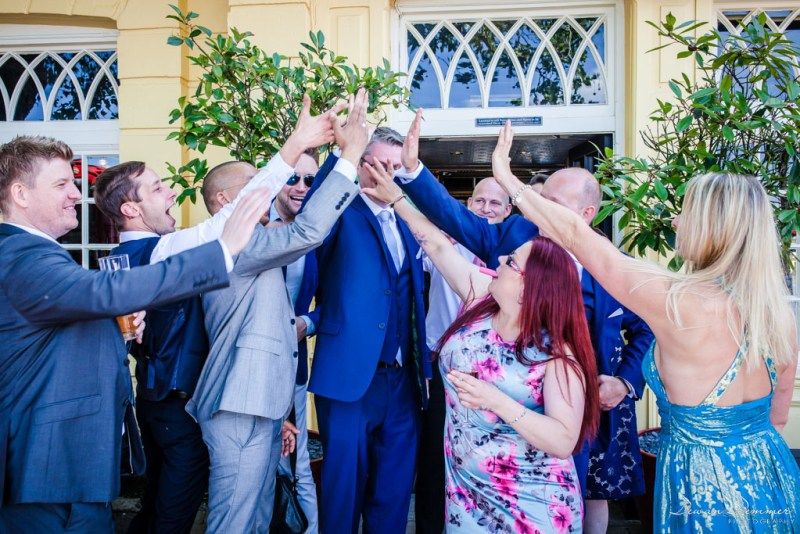 Groom getting a high five while bride gets ready
