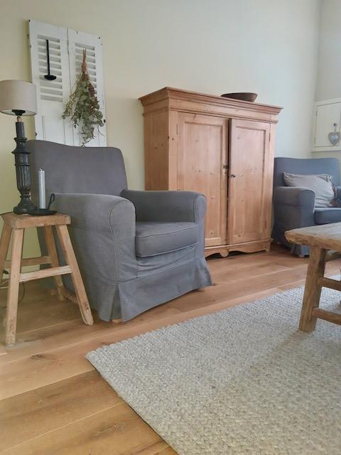 Grenen kast louvredeur grijze fauteuil balusterlamp houten kruk