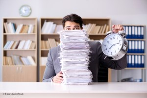 man behind paperwork with clock Elnur Adobestock