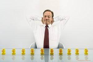 business man with rubber ducks in a row