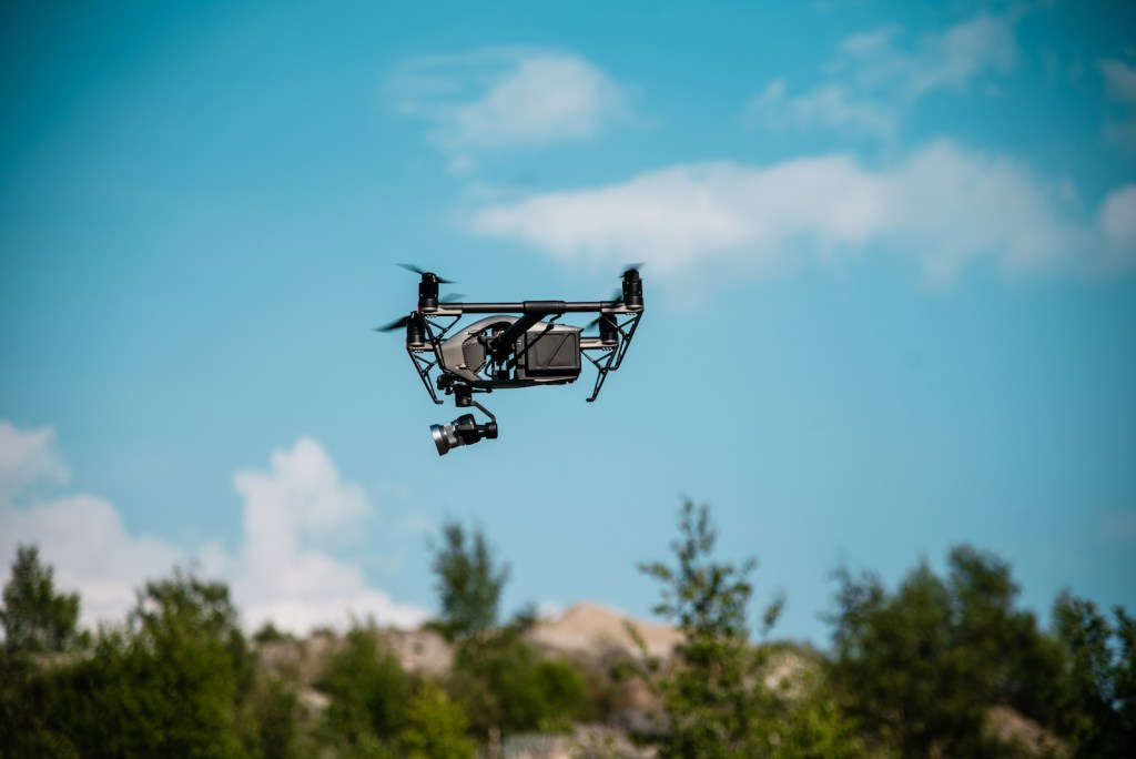 drone silhouetted against blue sky