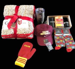 A basket full of Calvin University swag - fleece blanket, Nike hat, travel cup and coffee mugs, socks, and more!