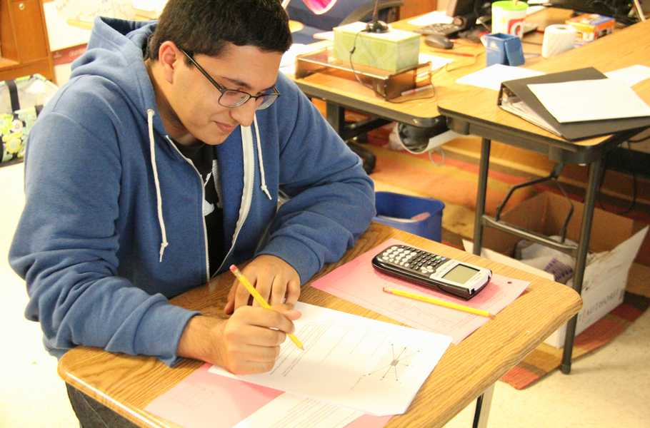 Doing a math assignment during class is Omar Akram. Omar was the schools lone student in advancing in the National Merit process.