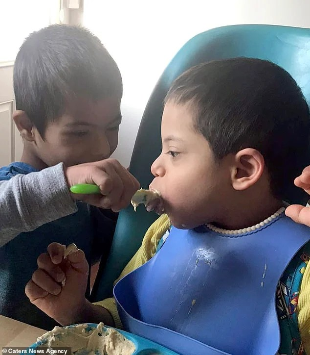 Since moving from Bulgaria last month, Simon helps his siblings eat using spoons and feeding syringes- seen feeding brother Alex,six, who also has Down's Syndrome