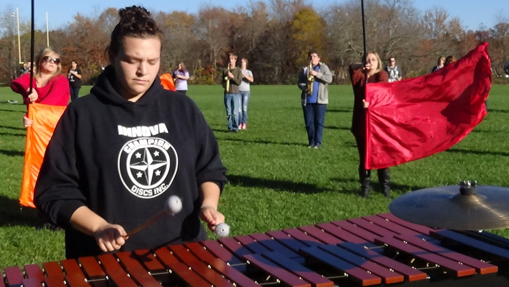 Percussionist Breanna Miller plays marimba as the Stone Memorial High School color guard and other band members run through their show finale during practice on Oct. 30, in Crossville, Tenn. (Photo by Diahan Krahulek / Full Sail University)