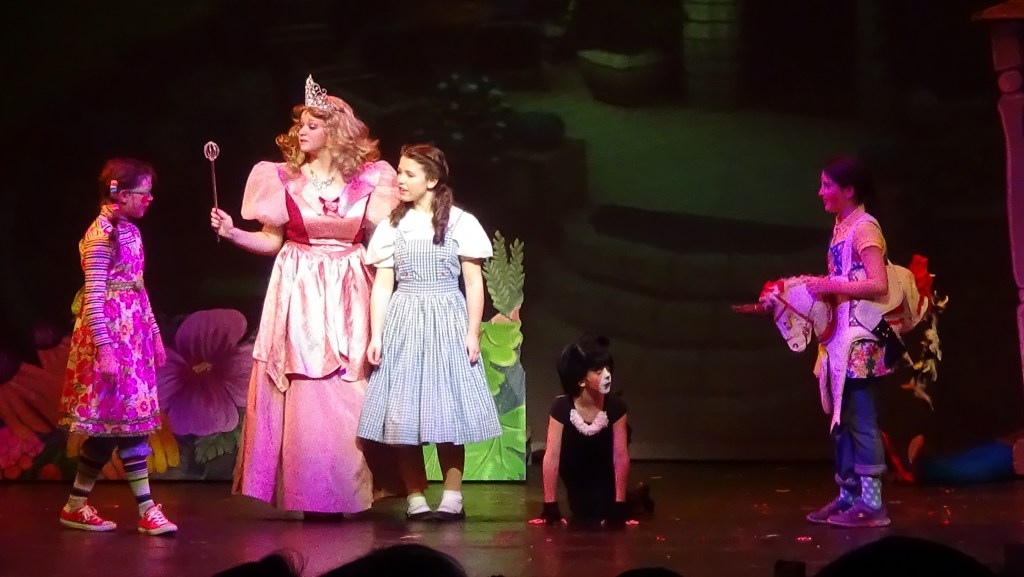 Good witch Glinda (Rachel Masters) and Munchkins greet Dorothy (Emery Smith) and Toto (Taylor Dearman) in Munchkinland. (Photo by Diahan Krahulek / Full Sail University)