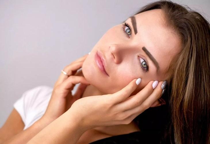 Eine Frau streichelt ihr Gesicht und zeigt ihre klare Haut.