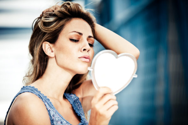 woman-looking-in-heart-shaped-mirror