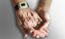 Aging parents 102: Image of younger hand holding older hand wearing an emergency alert bracelet.