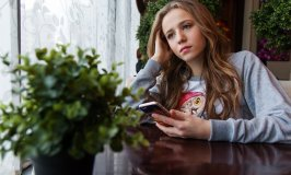 Keeping Kids Safe: image of sad teenaged girl with cell phone