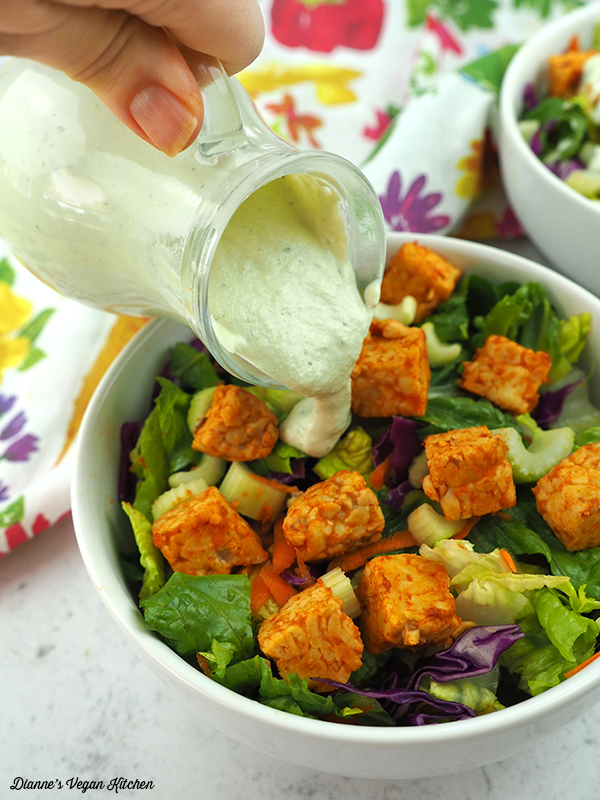 pouring ranch dressing over buffalo tempeh salad