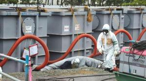 A worker walks in front of water tanks at the tsunami-crippled Fukushima Daiichi nuclear power plant in Fukushima prefecture in this June 12, 2013 file photo. Photo: Noboru Hashimoto/Reuters
