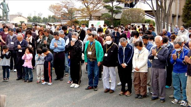 Residents of Futaba, exiled after the March 11, 2011 earthquake, tsunami, and nuclear disaster at Fukushima Daiichi Power Plant, gather in memorial, as seen in Nuclear Nation. – Reuters/First Run Features