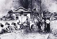 Victims of the first nuclear attack wait for treatment at the first-aid station near the Miyuki-bashi bridge in Hiroshima, about 2 km from the hypocentre of the explosion, at 11 a.m. on August 6, 1945. The Japanese city was bombed at 8-15 a.m. the same day.