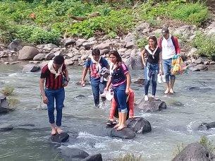 """Jóvenes que participaron de la """"Ruta del Combatiente"""" hacia el cerro de Guazapa, cruzan un río de la zona. Foto Diario Co Latino."""