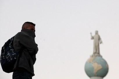 Un hombre espera en horas de la mañana en la Plaza de Las Américas o mejor conocido como Monumento al Divino Salvador del Mundo para salir con un grupo de personas hacia los Estados Unidos. Foto Diario Co Latino/ David Martínez.