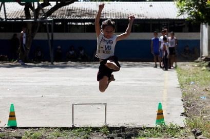 Una niña de El Painal, descalza y en una superficie no adecuada, practica salto de longitud. Foto Diario Co Latino/ David Martínez.