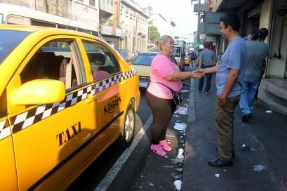 Roxana Rodas, saluda a uno de sus compañeros de trabajo durante su estadía en la base de taxis en la !ra cale Poniente de San Salvador. Diario Co Latino/ Ludwin Vanegas