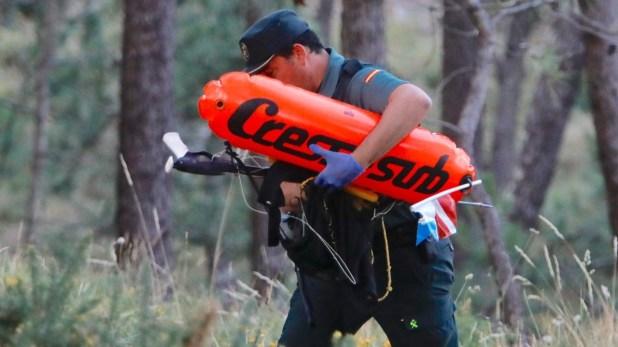 Un agente portando pruebas y efectos del submarinista fallecido. OUBIÑA