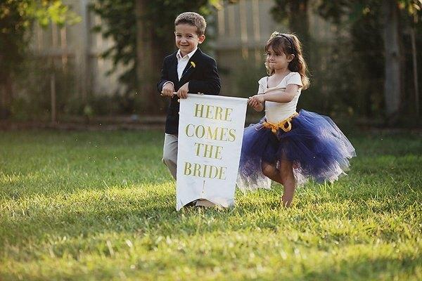 niños con cartel de aqui viene la novia