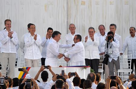 El presidente de Colombia, Juan Manuel Santos, y el jefe máximo de la guerrilla FARC, Rodrigo Londoño (Timochenko), firmaron este lunes un histórico acuerdo de paz para acabar con 52 años de confrontación armada