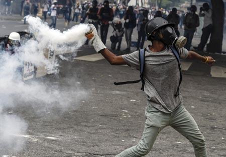 Jóvenes manifestantes encapuchados respondieron a las fuerzas de seguridad con piedras y cohetes explosivos, en choques que se registraron en varios puntos del este de Caracas