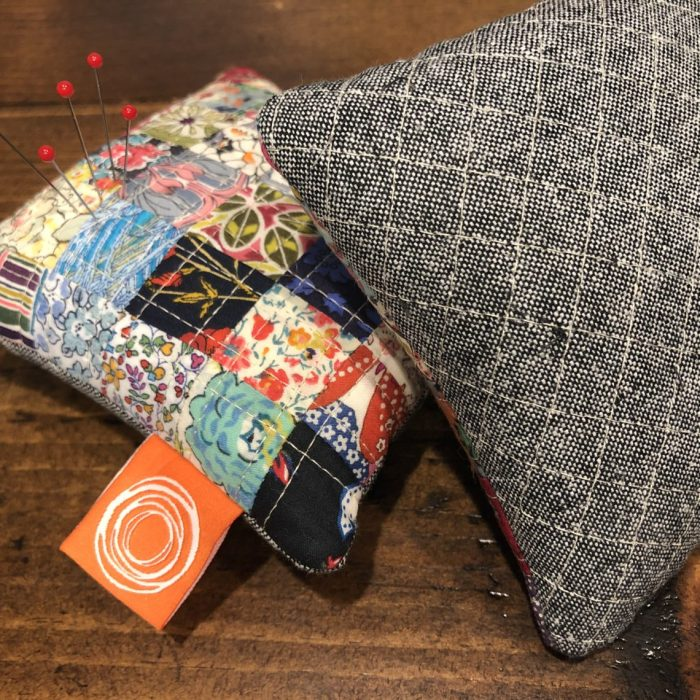 Patchwork Pincushions made with Liberty Lawns | Scrappy Liberty Patchwork Pincushion by Guest May Chappell by popular quilting blog, Diary of a Quilter: image of finished patchwork pincushion with pins in them.