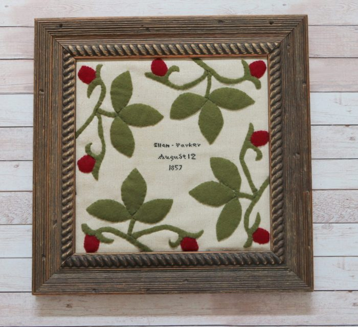 The Tale of a Pioneer Quilt, Cut in Two by popular quilting blog, Diary of a Quilter: image of a framed silk quilt block with wool felt strawberries stitched on it.