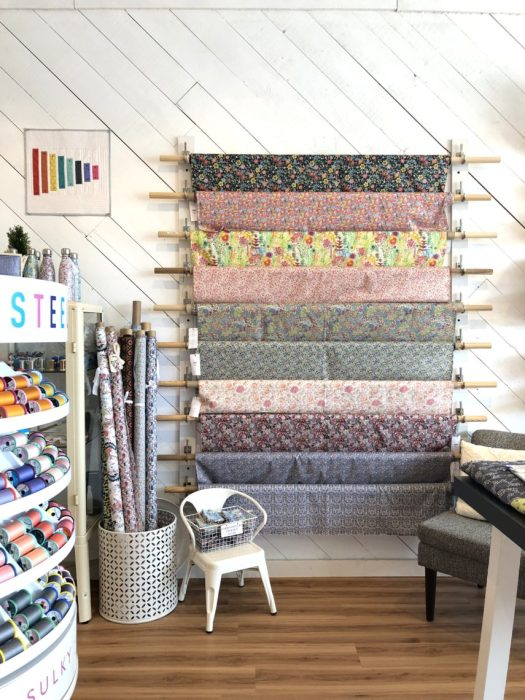 Pintuck & Purl - Modern Fabric and Knitting Shop by popular quilting blog, Diary of a Quilter: image of fabric yards hanging on a wall inside Pintuck and Purl.