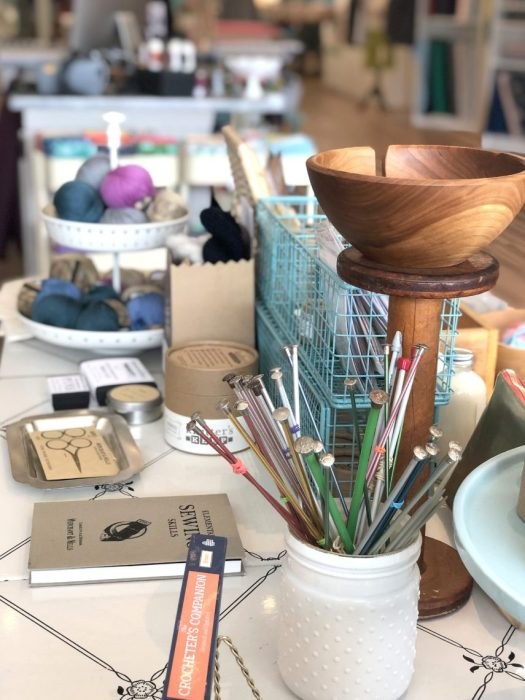 Pintuck & Purl - Modern Fabric and Knitting Shop by popular quilting blog, Diary of a Quilter: image of knitting needles, sewing scissors, and balls of yarn on a table inside Pintuck and Purl.