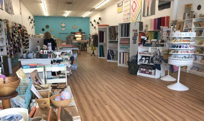 Pintuck & Purl - Modern Fabric and Knitting Shop by popular quilting blog, Diary of a Quilter: image of various spools of thread, knitting yarn, and fabric displays inside Pintuck and Purl.