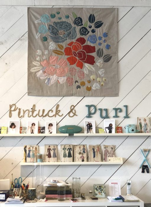 Pintuck & Purl - Modern Fabric and Knitting Shop by popular quilting blog, Diary of a Quilter: image of floral quilt hanging on a wall with some fabric patterns resting on shelves beneath it inside Pintuck and Purl.