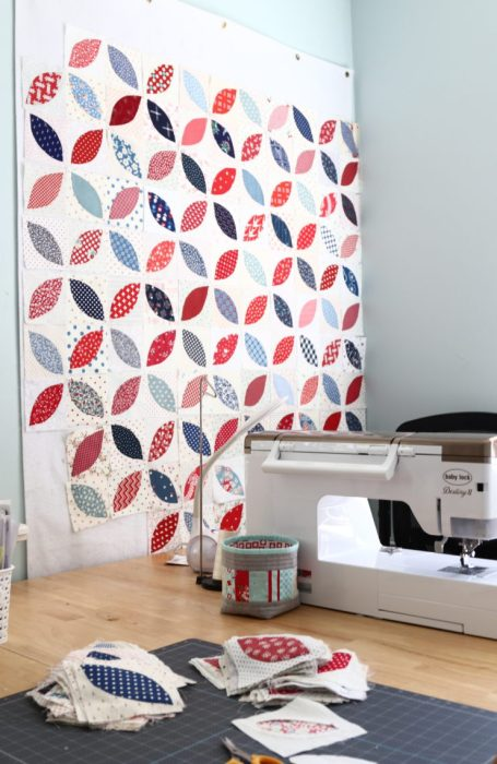 In Search of my Sewing Mojo and Other Tales of Summer by popular sewing blog, Diary of a Quilter: image of a sewing room with a white sewing machine on a table and red, white and blue block quilt on the wall.
