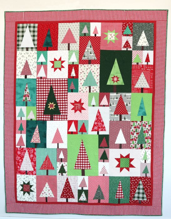 New Patchwork Forest Quilt Pattern: Pine Hollow Version by popular quilting blog, Diary of a Quilter: image of a red, white, and green patchwork forest tree quilt.