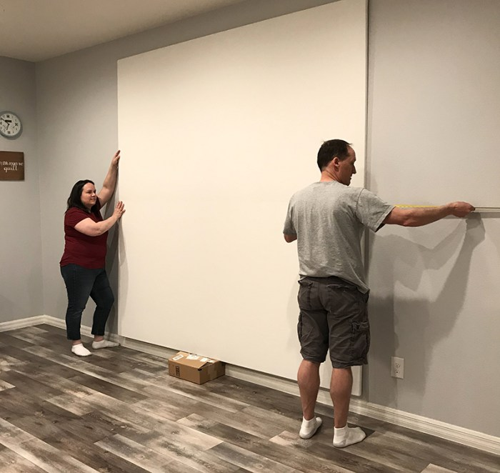 How to Build a Quilt Design Wall by Christa Watson by popular quilting blog, Diary of a Quilter: image of a man and woman attaching their quilt design board to a wall.