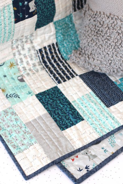 Bricks Baby Quilt Tutorial by popular quilting blog Diary of a Quilter: image of a various shades of blue bricks baby quilt draped over a crib railing.
