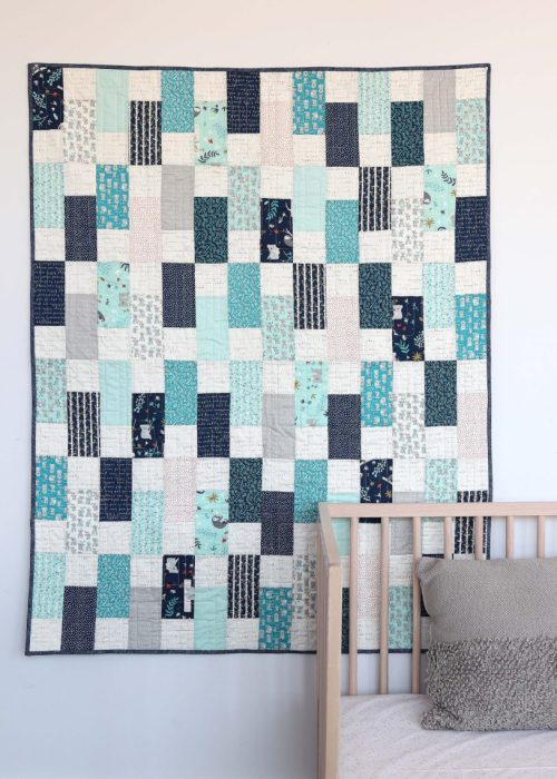Bricks Baby Quilt Tutorial by popular quilting blog Diary of a Quilter: image of a various shades of blue bricks baby quilt hanging on a wall behind a baby crib.