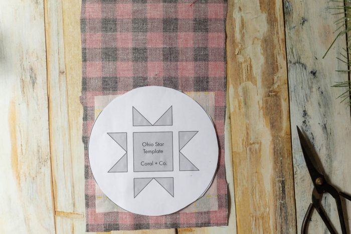 DIY Heirloom Christmas Ornament guest post by Coral + Co by popular Utah quilting blog, Diary of a Quilter: image of the backside of a piece of black and red plaid fabric with a square of Steam a Seam 2 on the bottom portion and an Ohio star template resting on top.