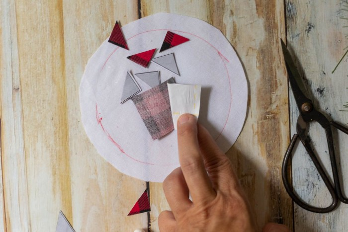 DIY Heirloom Christmas Ornament guest post by Coral + Co by popular Utah quilting blog, Diary of a Quilter: image of a woman peeling off Steam a Seam 2 paper from the back side of piece of an Ohio star pattern on black and red plaid fabric.