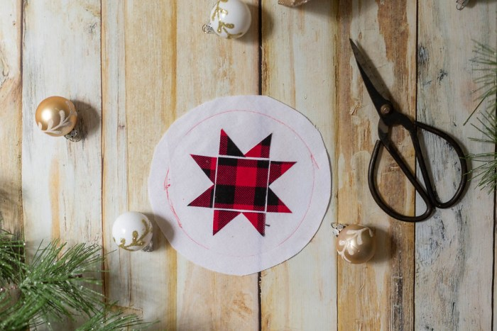 DIY Heirloom Christmas Ornament guest post by Coral + Co by popular Utah quilting blog, Diary of a Quilter: image of red and black plaid Ohio star laid on a round white piece of felt fabric.