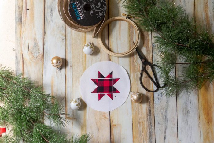 DIY Heirloom Christmas Ornament guest post by Coral + Co by popular Utah quilting blog, Diary of a Quilter: image of a round piece of white felt fabric with a red and black plaid Ohio star on it, embroidery hoop, twine, sewing scissors, and pine tree branches.