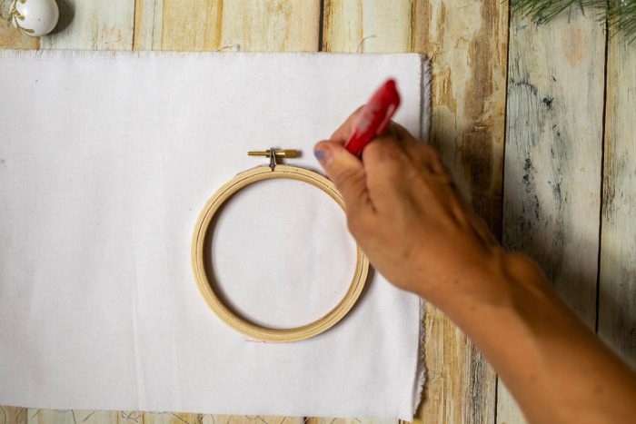 DIY Heirloom Christmas Ornament guest post by Coral + Co by popular Utah quilting blog, Diary of a Quilter: image of a woman tracing around an embroidery hoop with a red pen.