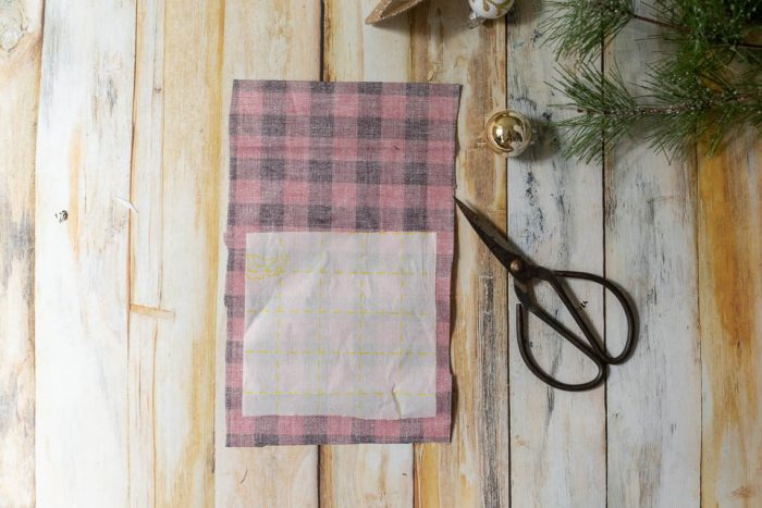 "DIY Heirloom Christmas Ornament guest post by Coral + Co by popular Utah quilting blog, Diary of a Quilter: image of some sewing scissors and the backside of some black and red plaid fabric with a 4"" square of Steam a Seam 2 on the lower half of the fabric."