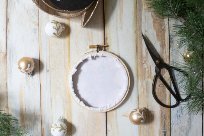 DIY Heirloom Christmas Ornament guest post by Coral + Co by popular Utah quilting blog, Diary of a Quilter: image of the backside of a finished embroidery hoop heirloom christmas ornament, sewing scissors, white and gold ornaments, and pine tree branches.